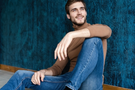 young casual fashion man sitting on the floor isolated on dark blue background. 스톡 콘텐츠