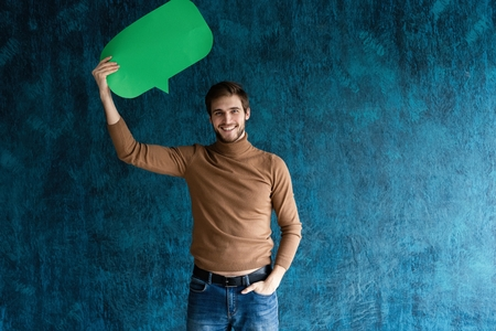 Lets start a conversation. I speak the language of success. Handsome young man holding up speech bubble isolated on dark blue. Stock Photo