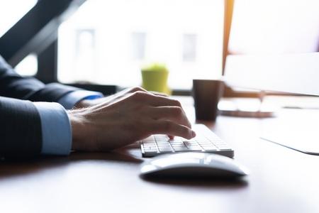 Business man using laptop computer. Male hand typing on laptop keyboard. Stock fotó