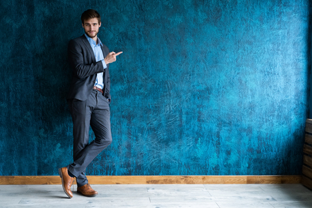 Full length portrait of young handsome businessman with smile pointing with finger. Stock Photo