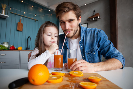 family, eating and people concept - happy father and daughter having breakfast at home 写真素材