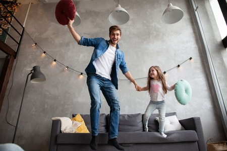 Funny father and cute kid daughter laughing jumping having fun in living room, active family enjoying moving playing with parent at home Stok Fotoğraf