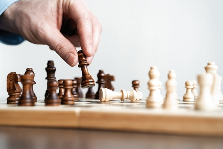 hand of businessman moving chess figure in competition success play. strategy, management or leadership concept.
