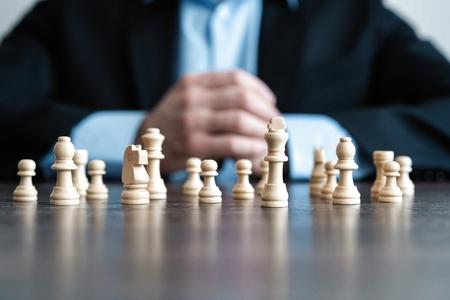 Geschäftsmann mit Planungsstrategie der gefalteten Hände mit Schachfiguren auf Tisch. Strategie-, Führungs- und Teamwork-Konzept.