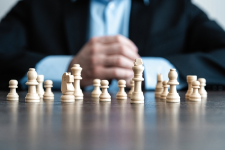 Businessman with clasped hands planning strategy with chess figures on table. Strategy, leadership and teamwork concept.