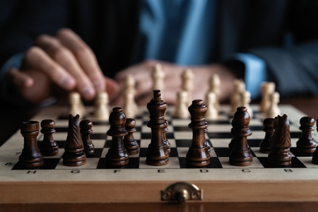 Un homme d'affaires joue avec un jeu d'échecs. concept de stratégie commerciale et tactique.