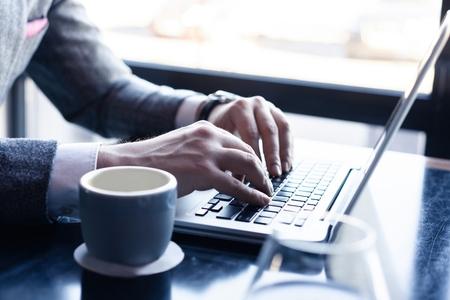 Junger Mann, der an seinem Laptop in einem Café arbeitet, Rückansicht der Geschäftsmannhände, die beschäftigt sind, Laptop am Schreibtisch zu benutzen.