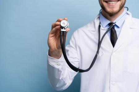 Médico joven hermoso que sostiene un estetoscopio, aislado sobre azul claro.