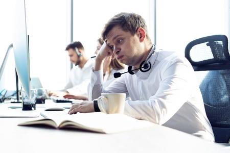 Zmartwiony lub zmęczony człowiek biznesu z zestawem słuchawkowym działa na komputerze w biurze.