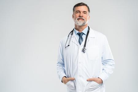Joyeux docteur mature posant et souriant à la caméra, aux soins de santé et à la médecine. Banque d'images