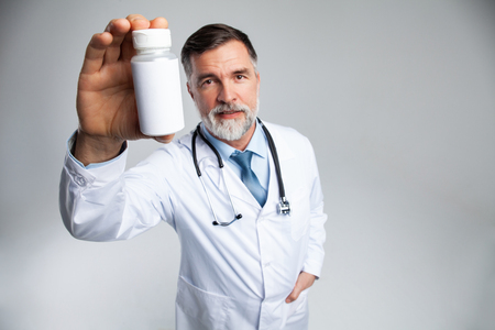 Smiling doctor holding up a bottle of tablets or pills with a blank white label for treatment of an illness or injury. Banco de Imagens