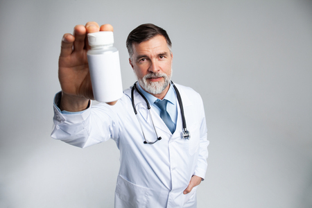 Smiling doctor holding up a bottle of tablets or pills with a blank white label for treatment of an illness or injury. Stock Photo