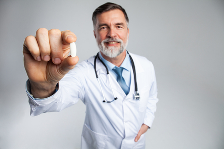 healthcare and medical concept - doctor with pill in hospital