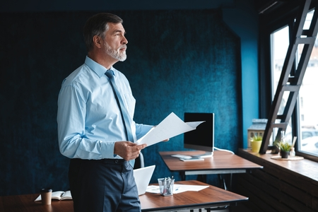 Focused concentrated accountant, mature businessman looking at the report, stands in full suit, so successful and intelligent, modern work station.
