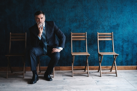 Waiting for interview. Confident mature businessman sitting on chair against dark blue background.