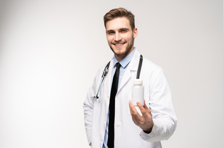 Smiling doctor holding a bottle of tablets or pills with a blank white label for treatment of an illness or injury. Фото со стока