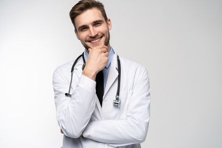 Smiling medical worker in white coat isolated on white. Stock Photo