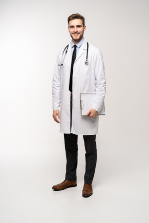 Full length young medical doctor on white background.