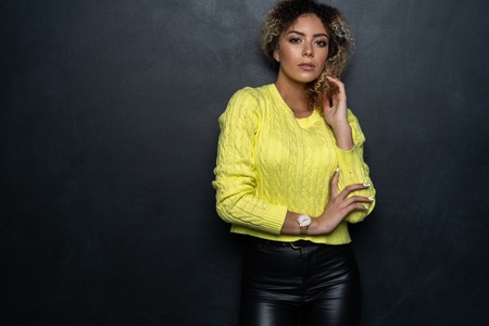 Portrait of a beautiful black female fashion model with curly hair over black background. Stockfoto