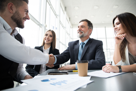 Business people shaking hands while working in the creative office Stock Photo