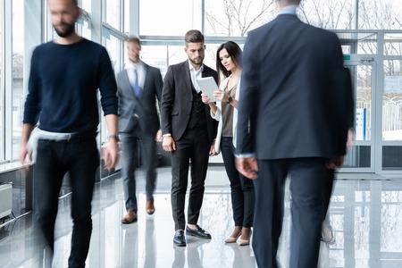 Pracownicy umysłowi idąc korytarzem biurowym podczas dnia roboczego.