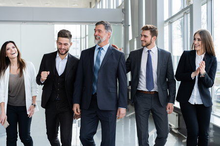 Business People Team Walking In Modern Office, Confident Businessmen And Businesswomen In Suits Diverse With Mature Leader In Foreground. Stock Photo