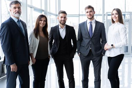 전체 길이의 자신감 있는 비즈니스 팀이 사무실에 서 있습니다.
