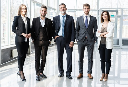 Full length confident business team stands in office. Banco de Imagens