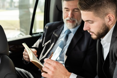 collègues de travail discutant d'idées commerciales assis à l'arrière de la voiture ou du taxi.