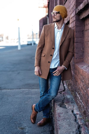 Portrait of stylish handsome young man in glasses with bristle standing outdoors. Man wearing jacket and shirt, leaning against wall.