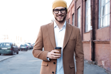 Handsome young man in casual wear holding disposable cup and smiling while walking through the city street.