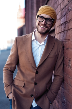 Portrait of stylish handsome young man in glasses with bristle standing outdoors. Man wearing jacket and shirt, leaning against wall. Stock fotó