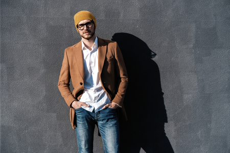 Portrait of handsome bearded man dressed in fashionable clothes standing on street against gray wall background