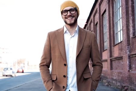 Portrait of stylish handsome young man in glasses with bristle standing outdoors. Man wearing jacket and shirt. Stock fotó