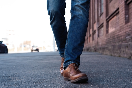 Male Legs In Jeans And Leather Boots Outdoor. Fashion Street Photo, color tone
