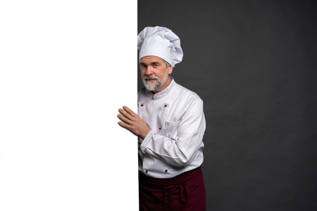 Portrait of a happy mature chef cook showing copyspace on the palms isolated on black background.
