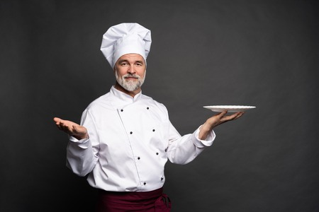 Mature cook chef holding an empty plate on a black background.