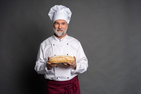 Male baker holding bread loaf and looking at camera isolated on black.