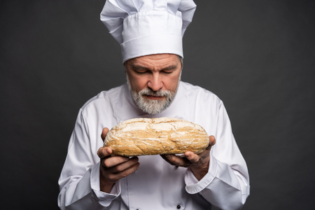 Portrait of a male chef cook smelling fresh bread against black background.