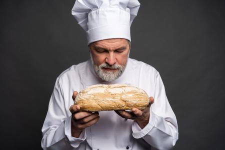 Ritratto di un cuoco maschio che sente l'odore del pane fresco su sfondo nero.