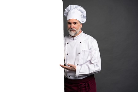 Portrait of a happy mature chef cook showing copyspace on the palms isolated on black background. 写真素材