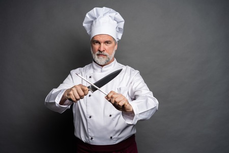 Portrait of a mature chef cook holding knifes isolated on a black background.
