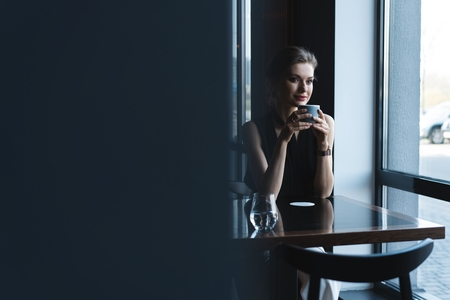 Portrait of gorgeous female drinking tea or coffee and looking with smile out of the coffee shop window while enjoying her leisure time Фото со стока