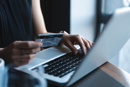 Hands of Woman shopping in Internet, making instant Payment Transaction at Computer, using Credit Card.