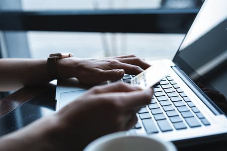 Manos de mujer de compras en Internet, realizando transacciones de pago instantáneas en la computadora, mediante tarjeta de crédito.