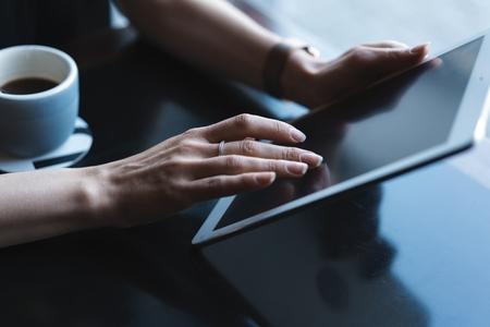 Cerca de manos mujer usando su tablet pc en restaurante, cafetería