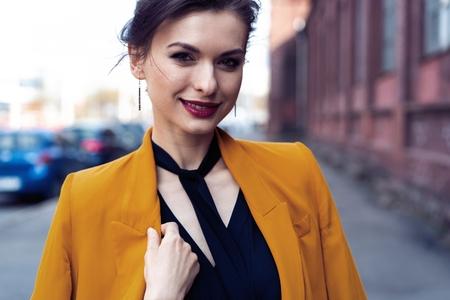 Portrait fashion woman walking on street . She wears yellow jacket, smiling to side.