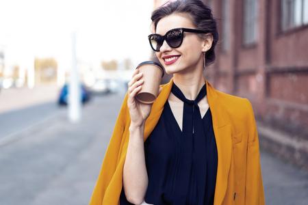 Portrait fashion woman in sunglasses walking on street . She wears yellow jacket, smiling to side.