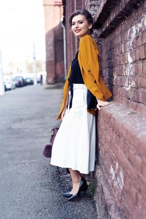 Portrait fashion woman walking on street . She wears yellow jacket, smiling to side. Stock Photo