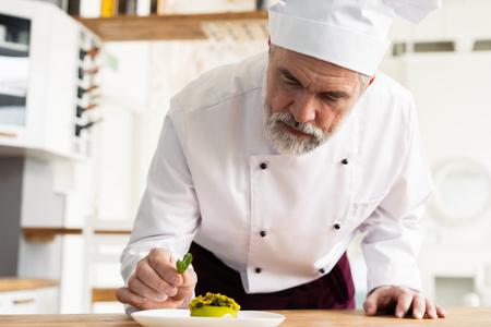 Bliska dekoracji cukiernik pyszne danie deserowe, służąc klientom w piekarni, przyozdobiając talerz deserowy w komercyjnej kuchni. Zdjęcie Seryjne